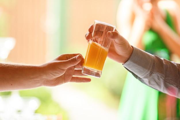 De hand van de mens reikt een glas met vers sap naar een andere man