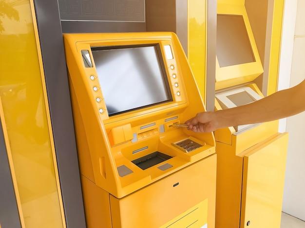 De hand van de mens steekt een atm-kaart in een geldautomaat van een bank.