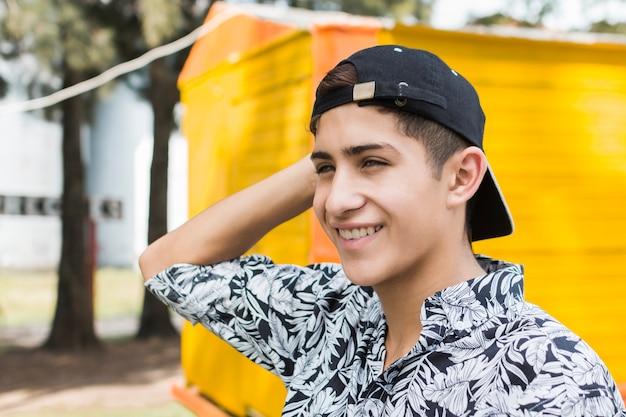 De hand van de modieuze het glimlachen tiener op zijn hoofd