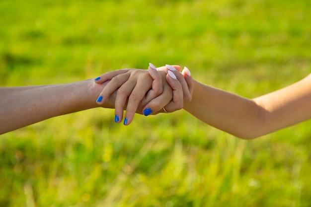De hand van de moeder leidt haar dochterkind in de zomerbosnatuur buiten, vertrouw op de nabijheid van het familieconcept
