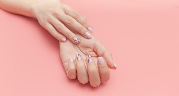 De hand van de mooie jonge vrouw met perfecte manicure op roze