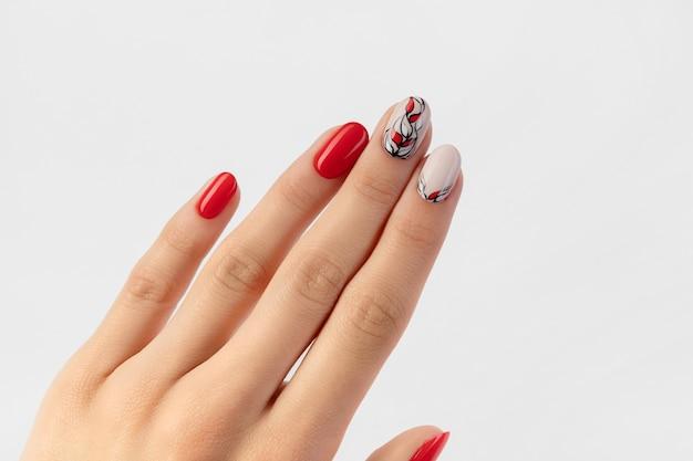 De hand van de mooie jonge vrouw met rode manicure op wit