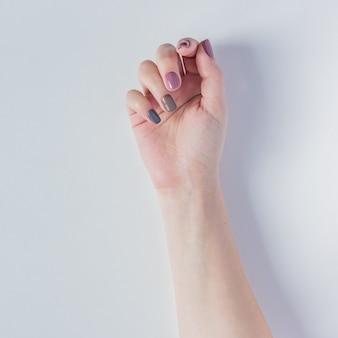 De hand van de mooie jonge vrouw op wit. stijlvolle trendy vrouwelijke manicure met grijze, roze en bruine nagellak. natuurlijke nagels