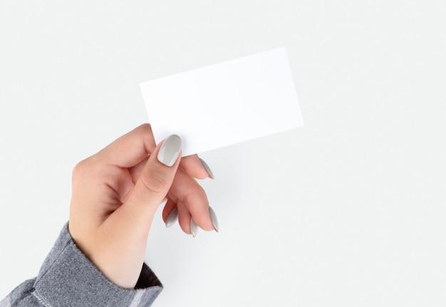 De hand van de mooie vrouw met het adreskaartje van de manicureholding