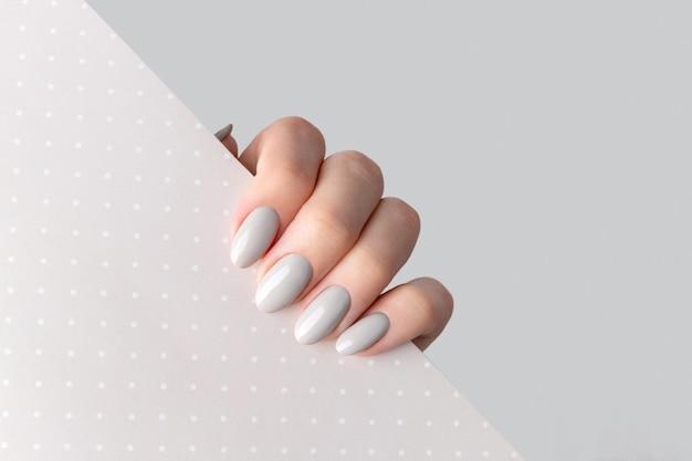 De hand van de mooie vrouw met manicure dichte omhooggaand op stipachtergrond. grijze nagellak