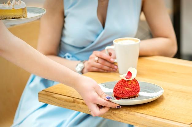 De hand van de ober legt op de tafel een bord met een rode cupcake op de achtergrond van een vrouwelijke klant in een café