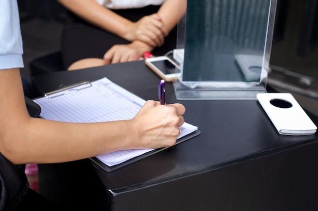 De hand van de onderneemster met pen die informatieformulier voltooien
