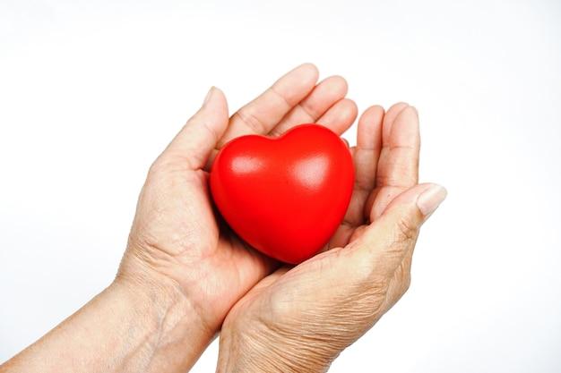 De hand van de oude vrouw die een rood hart vasthoudt, doneert, geeft liefde, warmte, wees voorzichtig