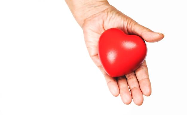 De hand van de oude vrouw die een rood hart vasthoudt, helpt om liefde te geven, warmte te geven. wereldgezondheidsdag. Premium Foto