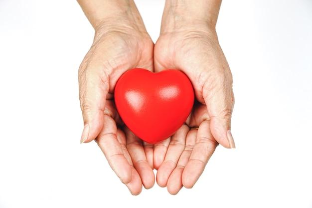 De hand van de oude vrouw die een rood hart vasthoudt, helpt om liefde te geven, warmte te geven. wereldgezondheidsdag.