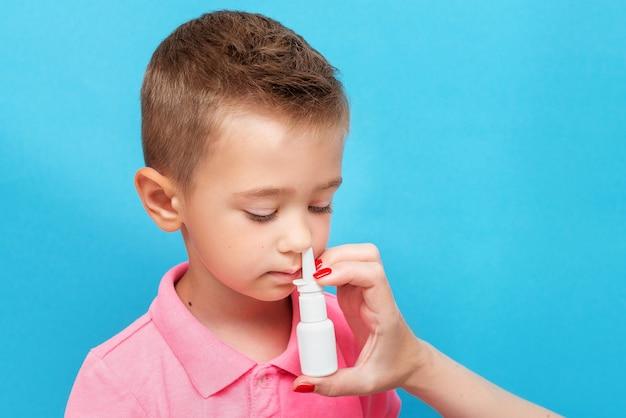 De hand van de ouder brengt een neusspray aan om de kleine jongen te genezen