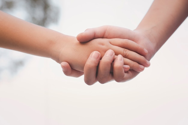 De hand van de oudere zus die de hand van haar zus bij elkaar houdt. vriendschap en veiligheid en liefde