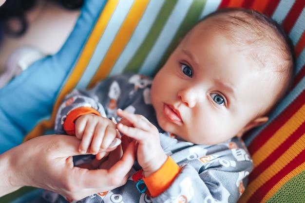 De hand van de pasgeboren baby van de kleine pasgeboren ouder