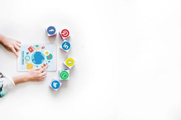 De hand van de persoon die digitale tablet met blokken van sociale media toepassingen gebruikt