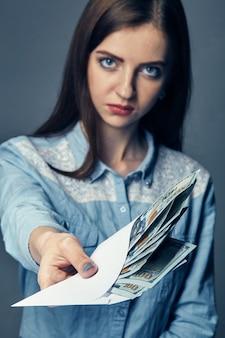 De hand van de persoon geeft steekpenningen in dollars. amerikaanse dollars in de hand. vrouw biedt geld op een donkere ondergrond. een stapel amerikaans geld in de hand op een donkere ondergrond.