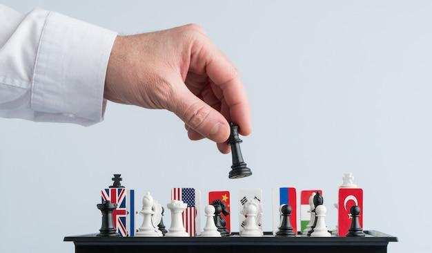 De hand van de politicus beweegt een schaakstuk. conceptuele foto van een politiek spel en strategie.