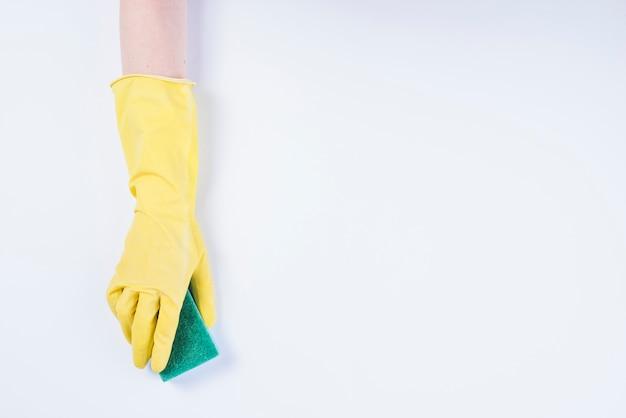 De hand van de portier met gele handschoenen die spons op witte achtergrond houden