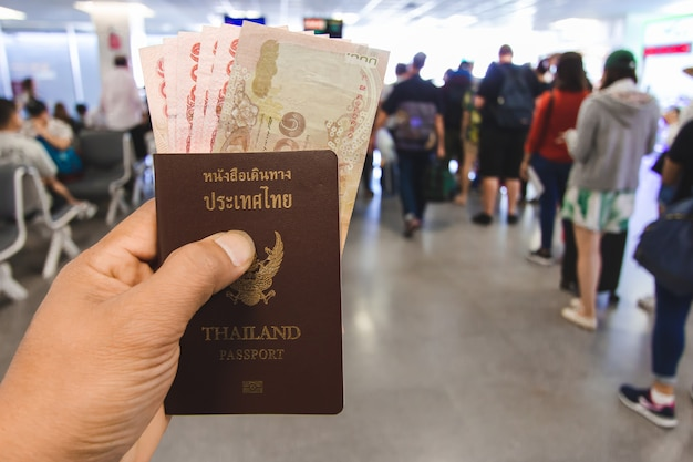 De hand van de reiziger houdt geld en paspoorten in thailand