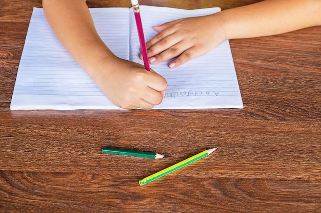 De hand van de student staat op papier op de schooltafel.