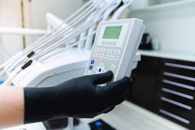 De hand van de tandarts in de zwarte handschoenen drukt op de bedieningsknoppen van de tandartsstoel. geneeskunde, stomatologie concept.
