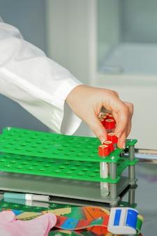 De hand van de technicus legt tests van lege bloedbuisjes op een rek in het laboratorium