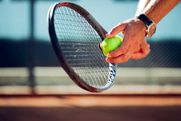 De hand van de tennisser die zich voorbereidt om een service te nemen