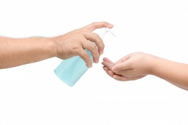 De hand van de vader het drukken fles en het gieten op alcoholbasis zuivert op handkind.