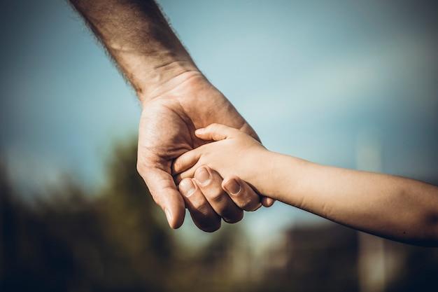 De hand van de vader leidt zijn kind in de zomeraard openlucht