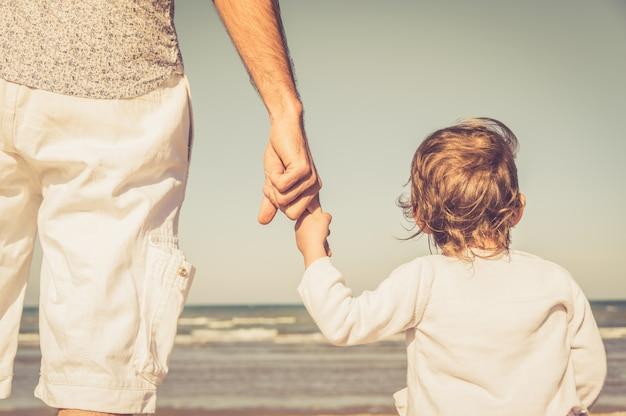 De hand van de vader leidt zijn kindzoon in de aard van het de zomerstrand openlucht, vertrouwt familieconcept