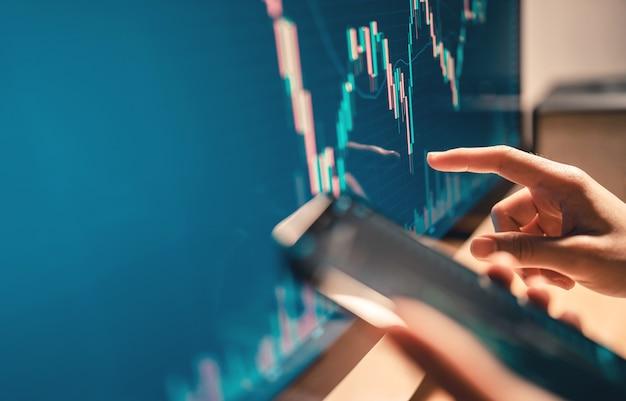 De hand van de vrouw controleert de bitcoin-prijsgrafiek op digitale uitwisseling op de computer