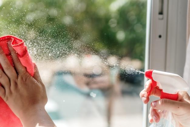 De hand van de vrouw die een ruit schoonmaakt met een oplossing voor het reinigen van ramen.