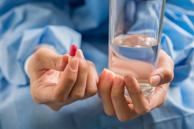 De hand van de vrouw giet de medicijnpillen uit de fles