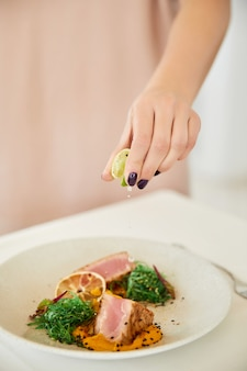 De hand van de vrouw giet met citroensap de tonijnmaaltijd