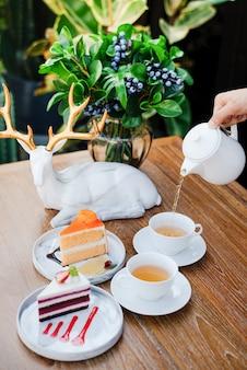 De hand van de vrouw giet 's ochtends hete thee en gebak.