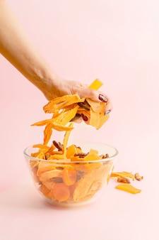 De hand van de vrouw grijpt een handvol gedroogd fruit uit een kom met een assortiment veganistische jerky.