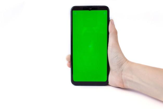 De hand van de vrouw houdt de smartphone in een verticale positie met een groen scherm op een witte achtergrond. chroma sleutel. bespotten