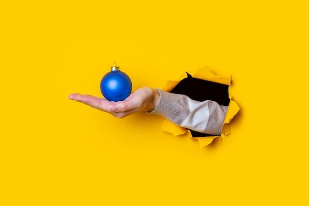 De hand van de vrouw houdt een blauwe decoratieve kerstbal op een gele achtergrond.