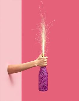 De hand van de vrouw houdt een geschilderde champagnefles met vakantievuurwerk op een duotone roze achtergrond, kopieer spase. kerstconcept.