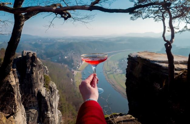 De hand van de vrouw houdt een glas champagne op de rivier de elbe in saksisch zwitserland