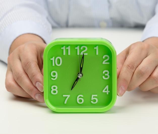 De hand van de vrouw houdt een groene vierkante wekker vast, de klok toont zeven uur 's ochtends. vroeg opstaan, de dag beginnen