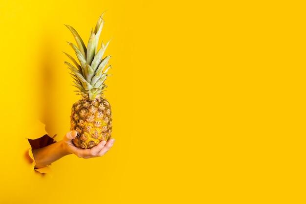 De hand van de vrouw houdt een hele ananas op een gescheurde gele achtergrond.
