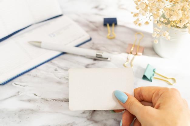 De hand van de vrouw houdt een leeg adreskaartje in het kantoor