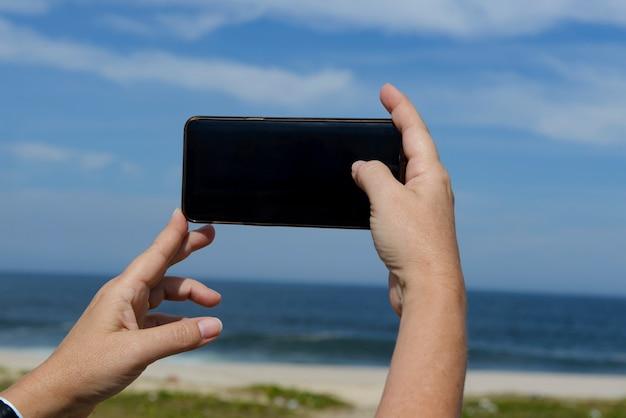 De hand van de vrouw houdt een mobiele telefoon vast om een foto van het strand te maken