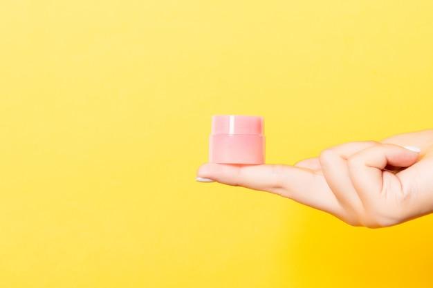 De hand van de vrouw houdt een potje cosmetica op geel