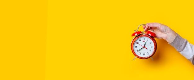 De hand van de vrouw houdt een rood horloge vast op een gele achtergrond. banier.