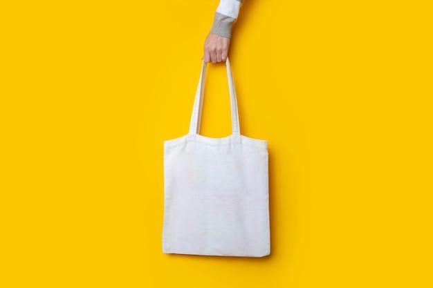 De hand van de vrouw houdt een stoffen eco-boodschappentas vast op een felgele achtergrond.