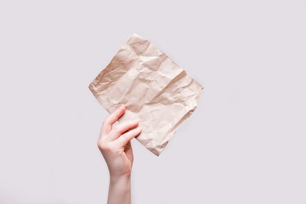 De hand van de vrouw houdt een stuk bruin inpakpapier vast