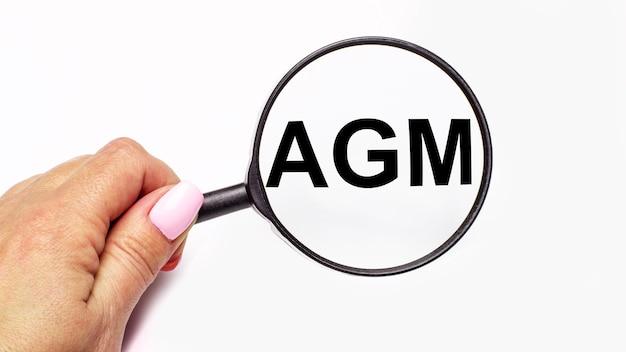 De hand van de vrouw houdt een vergrootglas met de inscriptie agm annual general meeting