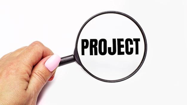 De hand van de vrouw houdt een vergrootglas met het opschrift project