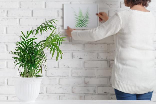 De hand van de vrouw houdt fotokader en concrete pot met huisinstallatie